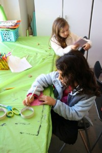 Samantha, 6, and Arielle, 5, simultaneously pencil out design for their respective printmaking projects.
