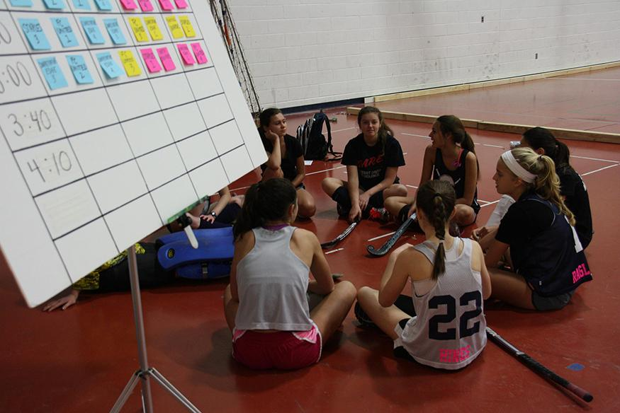 One of Staples' combined varsity, jv and freshman teams gather before a match. Next to them is a board with the arrangement of teams playing throughout the fieldhouse.