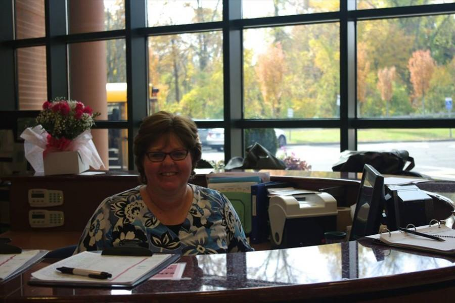 McQuone smiles from her  desk, greeting students on their way into school.