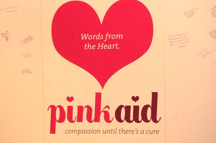 Pink Aid's motto surrounded by hand-written notes from attendees.