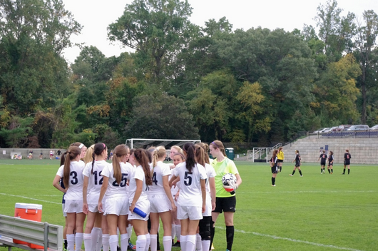 The girls huddle up for some pump-up words from the captains before they take the field.
