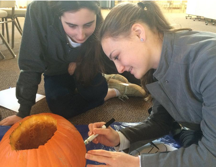 Staples students Annie Haroun '16 and Eliza Donovan '16 start the pumpkin carving process by outlining their idea.