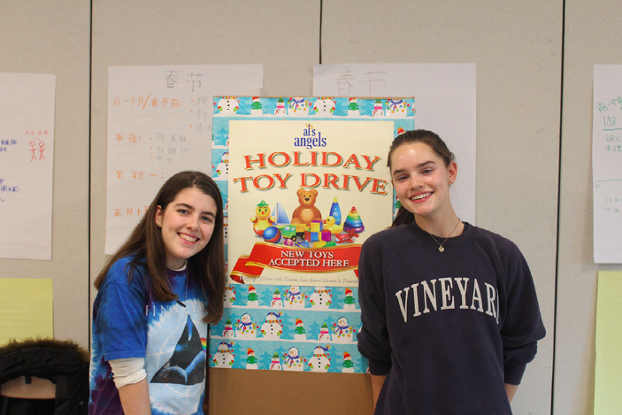 Merin McCallum '21 and Savannah Schaefer '21 pose next to the Holiday Toy Drive donation box