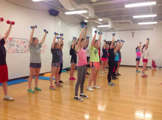 People work out in a gym wearing proper attire for their activity.