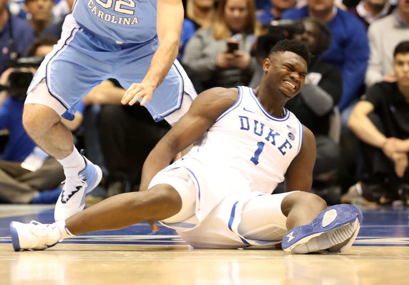 Luke Maye (32) gets the ball as Zion Williamson (1) falls after his foot cuts the bottom of his Nike shoe.