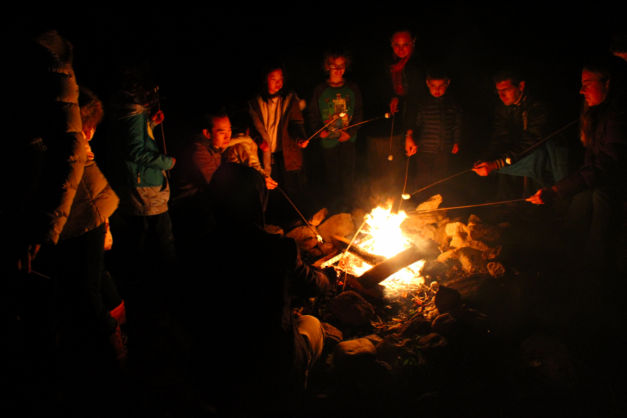 Friends and families gather around the Earthplace campfire, making s'mores and listening to spooky campfire stories.