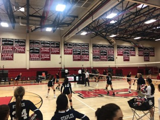 Staples girls' volleyball warms up for the game against New Canaan starting with their blocking routine and then moving into a passing drill, coached by John Shepro and Brendan Giolitto.