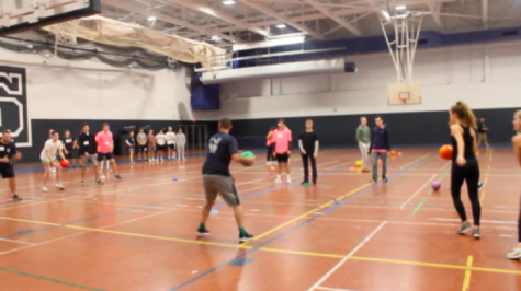 A police officer participating on a student team goes to throw the dodge ball after the game started.