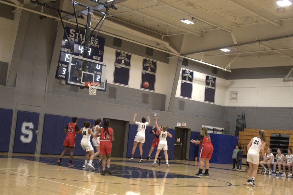 Caption: Keilani Lamourt '23 puts up a shot as she feels the defensive pressure from Marley Lopez-Paul '21 and Abby Carter '20 .