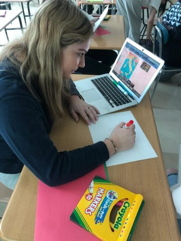 Ellee Seitz '21 works on posters to promote work language week during her honors Italian class. Many world language classes spent time making and hanging up posters around the school.