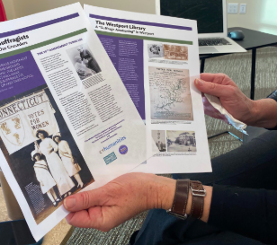 "Kathie Bennewitz, a curator for the WestportREADS exhibition ""Westport's Suffragists - Our Neighbors, Our Crusaders, displays an infographic by the Westport library about the upcoming exhibit."
