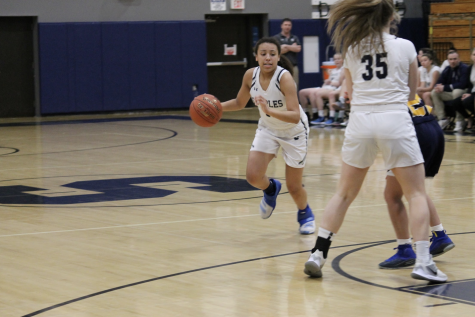 Nicole Holmes '21 taking the ball to the center of the court to try and make a layup.