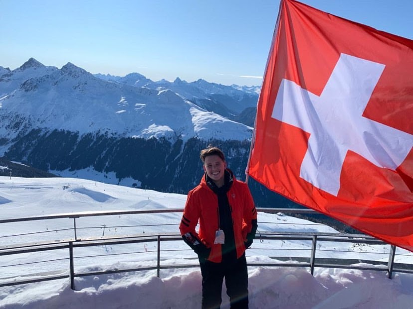 Dobin-Smith smiles next to flag of Switzerland during a quick exploration of the Swiss Alps. The group house he would share with other participants of the Wisdom Accelerator for Youth program is located across the valley.