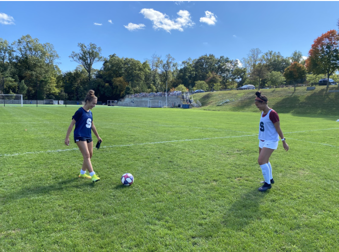 Arden Scherer and Charlotte Zhang warming up before soccer practice.