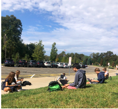 Students in a US History Honors class take advantage of good weather to learn while having a mask break outside.