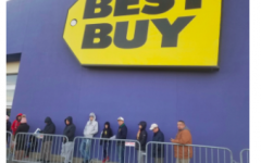 Black Friday, 2019. Customers line up outside Best Buy, waiting for the doors to open. Sales include items such as phones, headphones, cameras and computers.