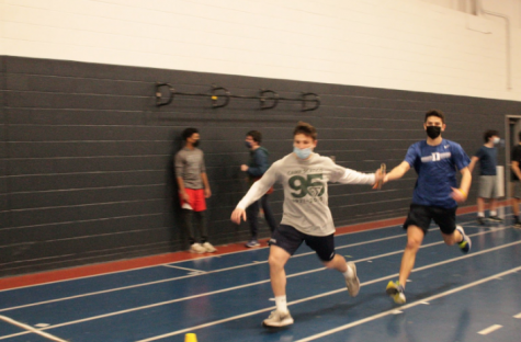 Henry Beck '21 receives the baton from Konur Nordberg '21 at a track and field practice. The track team is continuing to compete at a high level in virtual meets while regarding the COVID-19 rules.