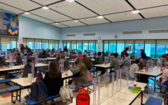 Maskless students eat lunch in a crowded cafeteria in a 75% capacity school model.
