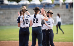 The Staples Varsity softball team high-fives last year before COVID-19 began. This year, social distancing and mask wearing will be enforced so on field play will be very different.