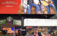 """(L-R), Cast members Griffin McIntyre and Jamie Mann '21 pose in front of the """"Country Comfort"""" billboard in Times Square, New York City."""