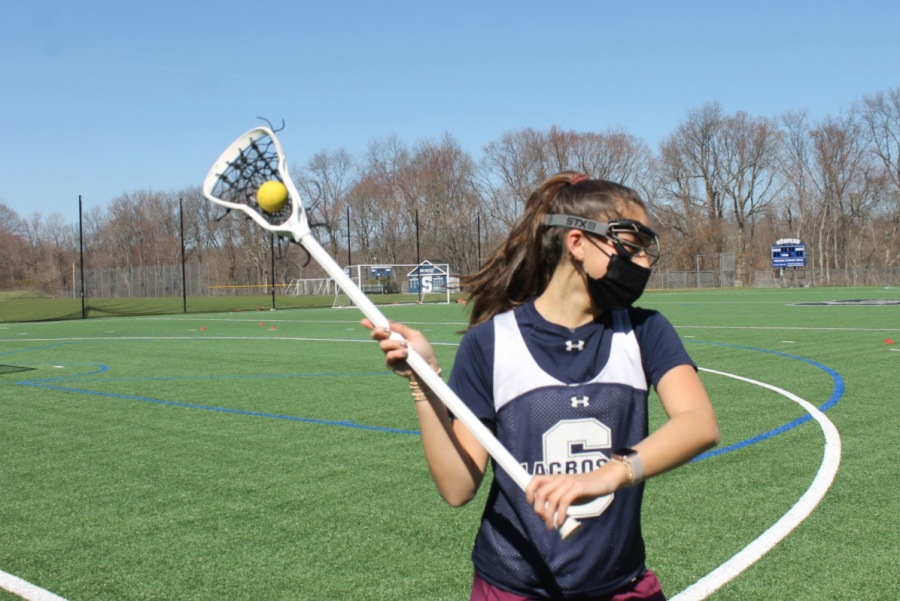 Girls' lacrosse captain Julia Diconza '21 gears up to pass the ball at tryouts for the 2021 season.