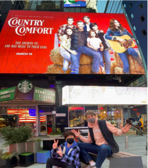 "(L-R), Cast members Griffin McIntyre and Jamie Mann '21 pose in front of the ""Country Comfort"" billboard in Times Square, New York City."