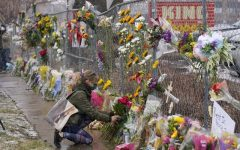 A woman kneels with flowers to pay tribute to the 10 victims of the Boulder, Colorado shooting on March 22.