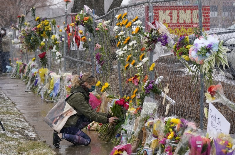 A+woman+kneels+with+flowers+to+pay+tribute+to+the+10+victims+of+the+Boulder%2C+Colorado+shooting+on+March+22.