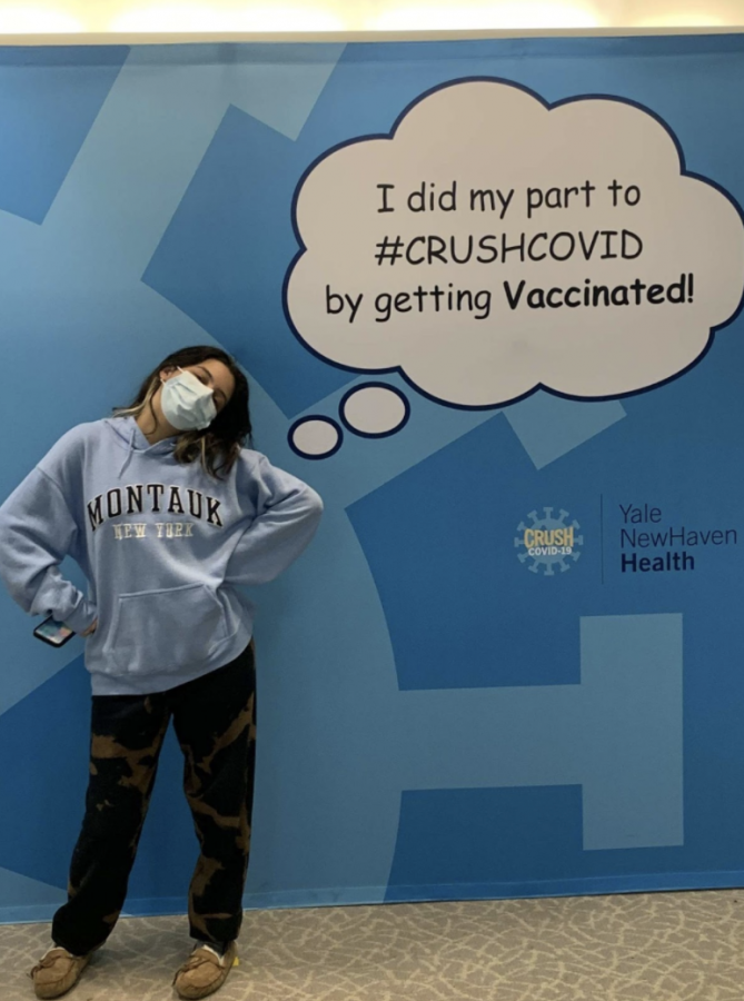 Sophie Spheeris '23 stands in front of a sign after receiving her second dose of the COVID-19 vaccination, only a couple of weeks after it opened up for 16 years and older.