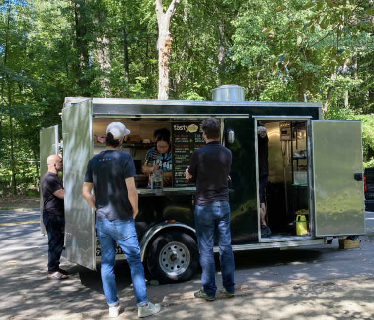 Customers order by the window of The Tasty Yolk food truck in Fairfield while the staff cooks and prepares everything from brussel sprouts to bacon and egg breakfast sandwiches.